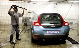 African Man washing a car at a underground carwash. Johannesburg, South Africa - April 27 2011: African Man washing a car at a underground carwash stock photo