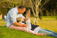 A couple relaxing on the grass at wine event royalty free stock photography