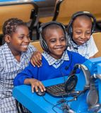 Kids looking at computer in school class room in Africa. royalty free stock photos