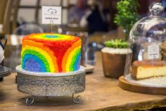Rainbow coloured cake on display. Brightly coloured icing. stock photos