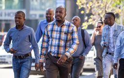 Men walking down street in Sandton city,. Johannesburg, South Africa - March 8, 2018: Men walking down road in city Stock Photography