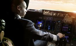 African Pilot flying a commercial airplane royalty free stock photos