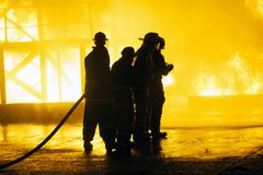 JOHANNESBURG, SOUTH AFRICA - MAY, 2018 Group of firefighters standing in front of fire during fighting training exercise Royalty Free Stock Image