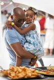 Girl in dads arms in daylight. royalty free stock photography