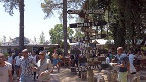 Directional signage in Fourways Farmers Market with people eating and socializing, Johannesburg, South Africa