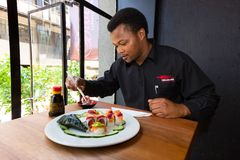 African Man eating Sushi in a Restaurant royalty free stock photos