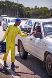 Street busker collecting tips from motorist. Johannesburg, South Africa, 29th March - 2019: Street dancer that performs at traffic intersection collecting a tip royalty free stock photos