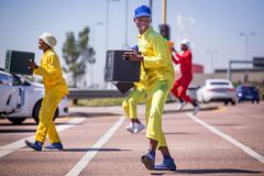 Pantsula dancers at traffic intersection. Johannesburg, South Africa, 29th March - 2019: Street dancers performing at traffic intersection with beer crates stock photography