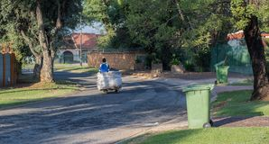 Recyclable products collected from household refuse bins. Johannesburg, South Africa - unidentified jobless man uses a makeshift trolley to collect recyclable stock image