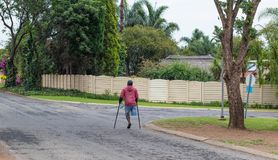 Unidentified physically disabled man on crutches. Johannesburg, South Africa - unidentified physically disabled man struggles on his crutches through a street in Royalty Free Stock Images