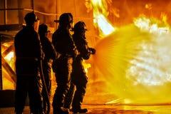 JOHANNESBURGO, SURÁFRICA - mayo de 2018 bomberos que rocían abajo del fuego durante un ejercicio de formación contraincendios imagenes de archivo