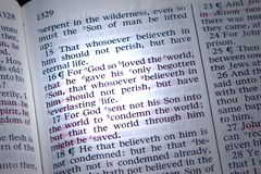 John 3:16. Bible is opened to John 3:16, highlighted by a beam of light Stock Images