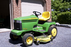 John Deere. Lawn mower in front of modest home Stock Image