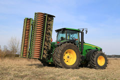 John Deere 8430 Agricultural Tractor with Ring Roller by Field Royalty Free Stock Image
