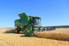 John Deere Combine s670i skördar korn på en Sunny Day royaltyfria foton