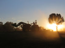 John Deere 5065E tractor working with loader and brush hog Stock Image