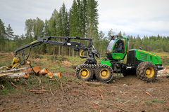 John Deere 1270E Wheeled Harvester in Forest. TAMMELA, FINLAND - AUGUST 31, 2014: John Deere 1270E wheeled harvester with chains at a forest logging site. The Royalty Free Stock Photo