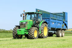 John deere green tractor pulling a trailer in grass field. Modern green  tractor pulling a blue trailer with crops in stubble field and big sky collecting silage Stock Photos