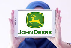 John deere logo. Logo of john deere brand on samsung tablet holded by arab muslim woman. john deere is an American corporation that manufactures agricultural Royalty Free Stock Photo