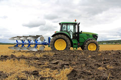 John Deere 6150M Tractor with a Plow on a Field Stock Photo