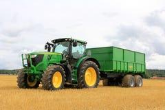 John Deere 6170R jordbruks- traktor och Palmse släp 1900 arkivfoton