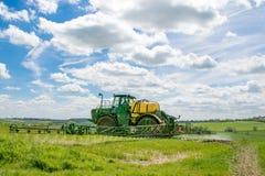 John Deere-Sprüher, der auf dem Weizengebiet sprüht Lizenzfreie Stockfotos