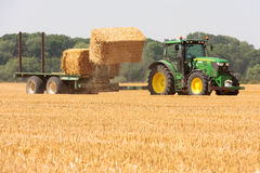 John Deere tractor collecting bales of straw Stock Images