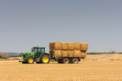 John Deere tractor collecting bales of straw Stock Image