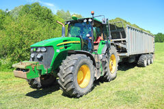 The John Deere 7930 tractor with the dumping Fliegl Gigant ASW 393 semi-trailer Stock Image