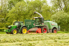 A John Deere tractor with Fendt Katana 65 forager. A green John Deere tractor with Fendt Katana 65 forager harvester harvesting silage Royalty Free Stock Photography