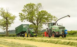 A John Deere tractor with Fendt Katana 65 forager. A green John Deere tractor with Fendt Katana 65 forager harvester harvesting silage and bailey trailer tipping Royalty Free Stock Images