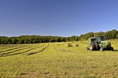 John Deere tractor in field with hay bales Royalty Free Stock Images
