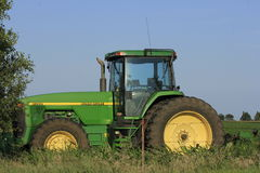 John Deere Tractor in a field. A John Deere tractor that's in a field, with blue sky, fence,tree, and grass thats bright and colorful Stock Photos