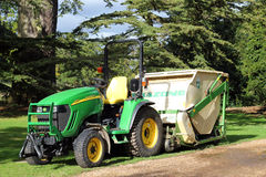 John deere tractor with a grass cutter. A small John Deere tractor towing an amazone grass cutter parked in a large park Stock Photos