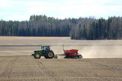 John Deere Tractor och Seeder på arbete på fält Royaltyfri Foto