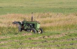 John deere tractor. An old vintage john deere tractor still hard at work in a ranchers field stock photos