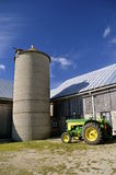 John Deere tractor parked by old barn Stock Image