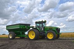 John Deere 7920 tractor pulling a gravity grain box. COMSTOCK, MINNESOTA, August 1, 2017: The John Deere 7920 pulling a gravity grain box is a product of John Royalty Free Stock Image