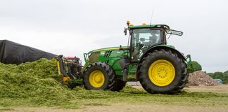 John Deere tractor pushing silage at the clamp royalty free stock images