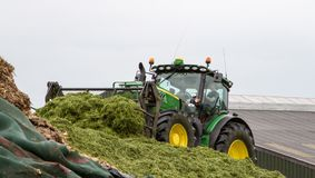 John Deere tractor pushing silage at the clamp. John Deere tractors clamping pushing grass silage into pit or clamp in dairy farm yard for cow food Royalty Free Stock Photos