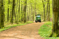 John Deere tractor. Ronneby, Sweden - May 11, 2015: Small John Deere compact utility tractor 2520 used in the forest on narrow path. Here seen with a trailer in Stock Photo