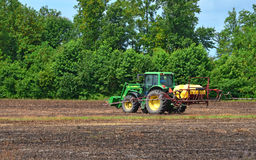 John Deere Tractor with Sprayer. John Deere tractor sitting in a burnt off field in the country of North Carolina while taking a break after spraying the fields Royalty Free Stock Photo