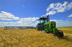 John Deere Tractor and swather in wheat field. Royalty Free Stock Photos