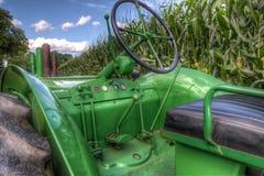 John Deere Tractor verde antiguo en campo de maíz fotos de archivo