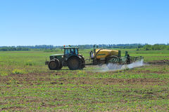 The John Deere tractor works with a hook-on sprayer. In the field Royalty Free Stock Photography