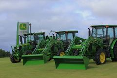John Deere Tractors bright green at a Dealer. A John Deere Dealer with three John Deere tractors sitting out front. Two with loader buckets. And one tractor Royalty Free Stock Photography