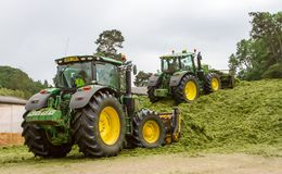 John Deere tractors pushing silage at the clamp stock photography