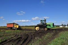 John Deere-Traktor, der LKW der roten Rübe im Schlamm zieht Stockfoto