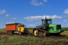 John Deere-Traktor, der LKW der roten Rübe im Schlamm zieht Lizenzfreie Stockfotos
