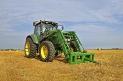 John Deere traktor i fält med sugrörbaler royaltyfri bild